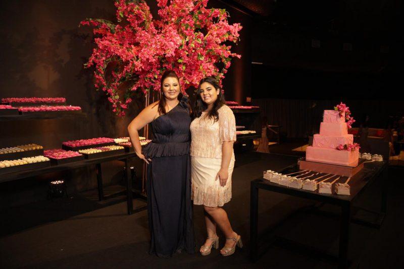 Maria Betânia Tiburcio, que envergou um modelo Lúcia Spessato, ao lado da filha, e com o belo arranjo floral e mesa de doces ao fundo.Foto: Canal R
